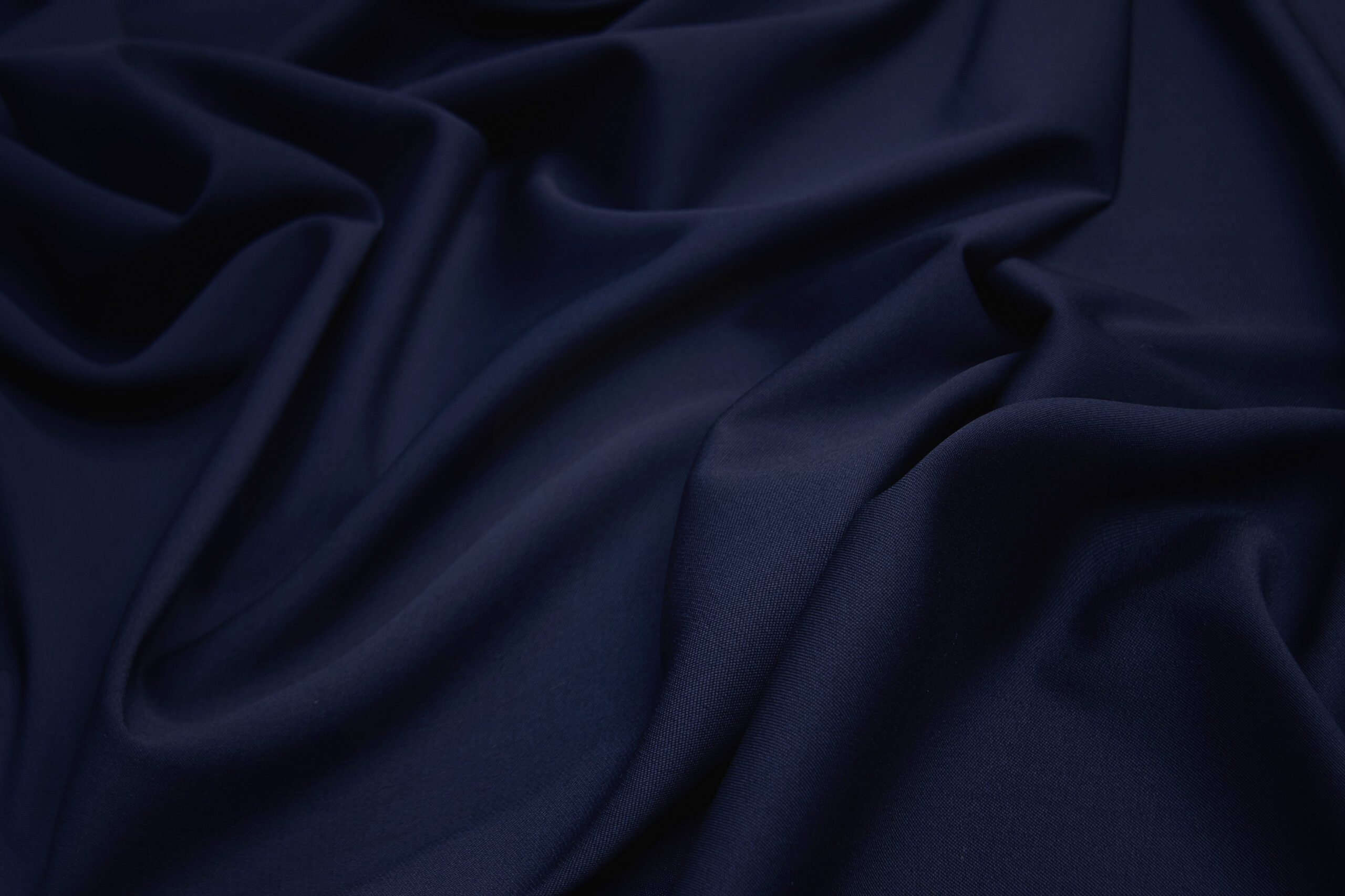 Luxurious woolen fabric in dark blue. Background and pattern.